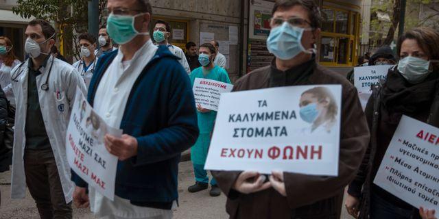 """Sjukvårdspersonal i Grekland kräver mer resurser. På skylten står det """"Även täckta munnar har en röst"""".  Petros Giannakouris / TT NYHETSBYRÅN"""