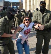 En kvinna förs bort under protester i Minsk. TT NYHETSBYRÅN