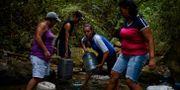 Männsikor bunkrar vatten i Caracas, Venezuela  FEDERICO PARRA / AFP