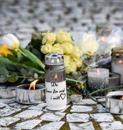 Människor har lagt blommor och tänd ljus på torget i Vårby gård för att hedra den 60-årige man som dog. Anders Wiklund/TT / TT NYHETSBYRÅN