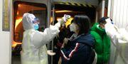 Människor som anländer från Wuhan undersöks vid flygplatsen i Peking. Emily Wang / TT NYHETSBYRÅN