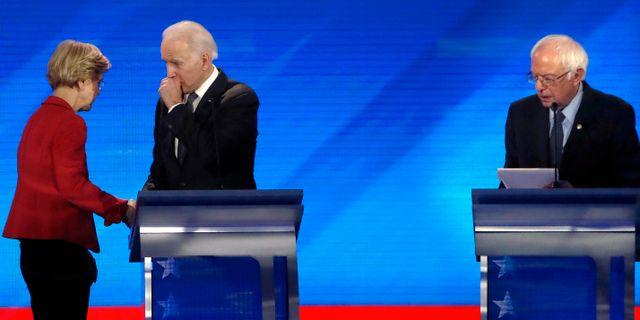 Arkivbild: Elizabeth Warren och Joe Biden i samspråk vid debatten i New Hampshire. Till höger: Bernie Sanders.  Elise Amendola / TT NYHETSBYRÅN