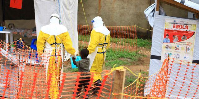 Räddningspersonal med en pojke som tros vara smittad. Al-hadji Kudra Maliro / TT NYHETSBYRÅN/ NTB Scanpix