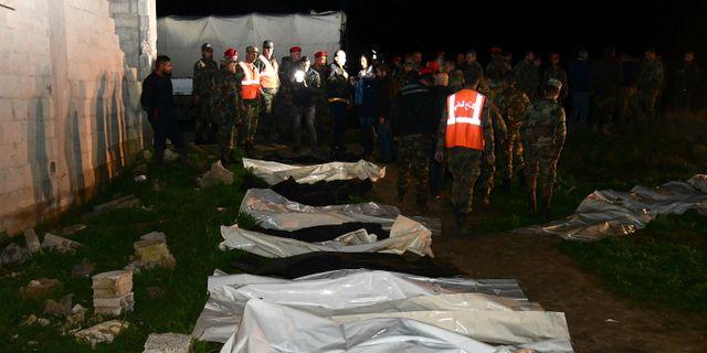 Syriska säkerhetsstyrkor vid den upphittade massgraven. TT NYHETSBYRÅN