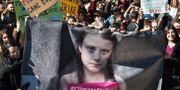 Klimataktivister med en banderoll av Greta Thunberg. ANDREAS SOLARO / AFP