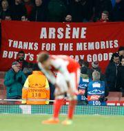 Arsenals Alex Oxlade-Chamberlain deppar. I bakgrunden håller Arsenal-supportrar upp en banderoll som kräver tränaren Arsène Wengers avgång. Frank Augstein / TT NYHETSBYRÅN