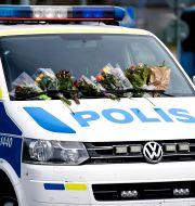 Blommor på en polisbil i Biskopsgården.  Björn Larsson Rosvall/TT / TT NYHETSBYRÅN