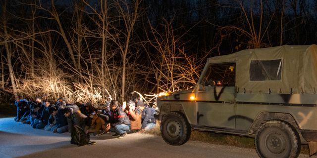 Grekisk militär och en grupp migranter vid gränsen. STRINGER / TT NYHETSBYRÅN