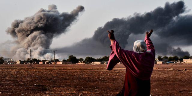 En kvinna bevittnar rök som stiger från staden Kobane. ARIS MESSINIS / AFP
