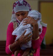 En kvinna i Indien håller sitt nyfödda barn Anupam Nath / TT NYHETSBYRÅN