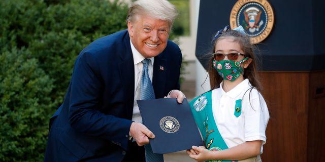 Trump poserar med en flickscout vid en ceremoni i Vita husets trädgård. Alex Brandon / TT NYHETSBYRÅN