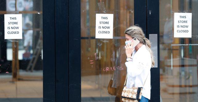 Illustrationsbild: Kvinna går förbi stängd affär i London, Storbritannien (juli 2020).  Alastair Grant / TT NYHETSBYRÅN
