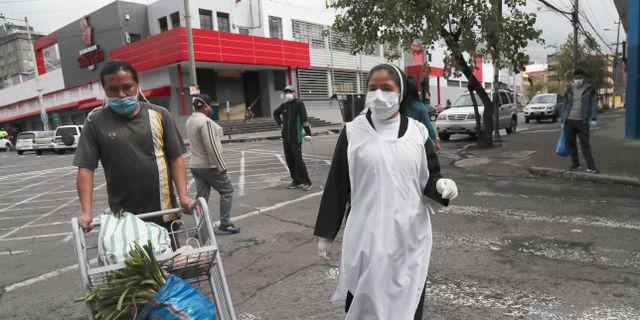Nunna i Ecuador iförd ansiktsmask och plasthandskar.  Dolores Ochoa / TT NYHETSBYRÅN