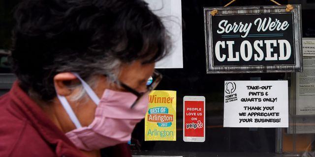 Illustrationsbild. En kvinna går förbi en stängd affär i Arlington, Virginia.  OLIVIER DOULIERY / TT NYHETSBYRÅN
