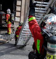 Räddningstjänst på plats vid banken som sattes i brand. GEOFFROY VAN DER HASSELT / AFP