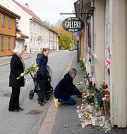 Människor lägger blommor vid en minnesplats i Kongsberg.  Terje Bendiksby / TT NYHETSBYRÅN