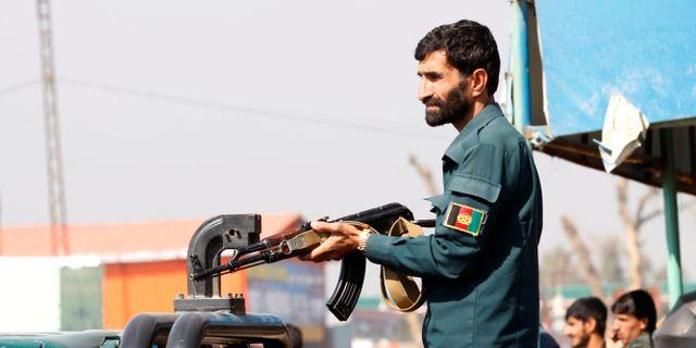 Afghansk polis positionerar sig nära attentatsplatsen i Jalalabad.  PARWIZ / TT NYHETSBYRÅN