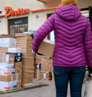 En kvinna hämtar ett paket i Stockholm. Utlämningsstället var tvunget att lägga paketen utanför butiken på grund av den ökande e-handeln i julas. Anders Wiklund/TT / TT NYHETSBYRÅN