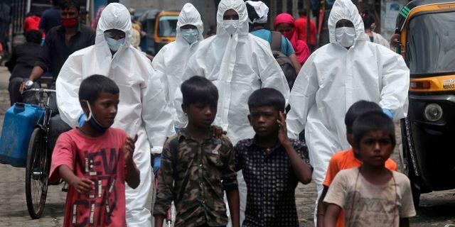 Sjukvårdspersonal i skyddsutrustning på väg att screena invånare i ett av Bombays slumområden. Rafiq Maqbool / TT NYHETSBYRÅN