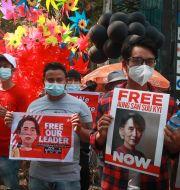 Demonstranter stöttar Aung San Suu Kyi.  TT NYHETSBYRÅN