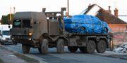 Ett fordon inslaget i blå pressening transporteras bort från en by norr om Salisbury. Ben Birchall / TT NYHETSBYRÅN