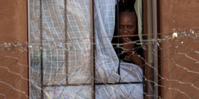 En kvinna tittar ut genom fönstret i statsdelen Diepsloot i norra delarna av Johannesburg.  Themba Hadebe / TT NYHETSBYRÅN