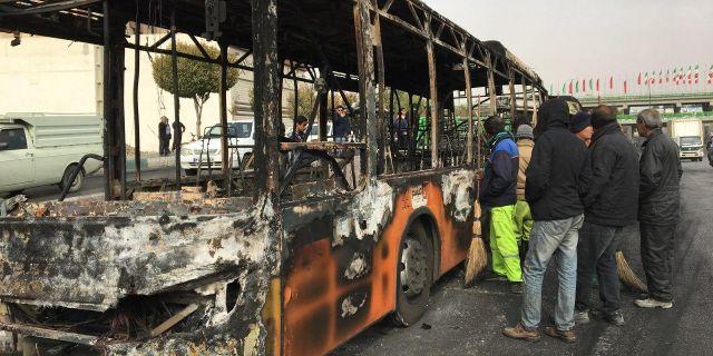 Iranier inspekterar en nedbrunnen buss. - / AFP