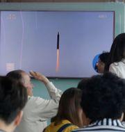 Personer i Sydkorea ser bilder av Nordkoreas robottest på tv.  Ahn Young-joon / TT NYHETSBYRÅN