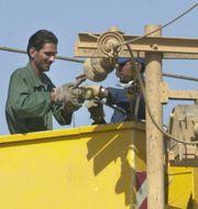 Arkivbild på en elektriker som jobbar med ledningarna i Iraks huvudstad Bagdad. HUSSEIN MALLA / TT NYHETSBYRÅN