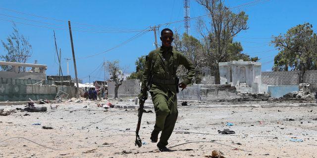 En somalisk soldat springer för att ta täckning under attacken i Mogadishu.  FEISAL OMAR / TT NYHETSBYRÅN