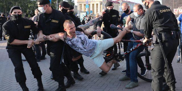 Belarusisk polis som håller en demonstrant. STR / TT NYHETSBYRÅN