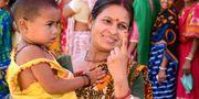 En indisk kvinna håller upp sitt finger för att visa märket som visar att hon röstat. NARINDER NANU / AFP