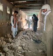 Människor försöker skyffla bort bråte efter fredagens explosion.  Sidiqullah Khan / TT NYHETSBYRÅN