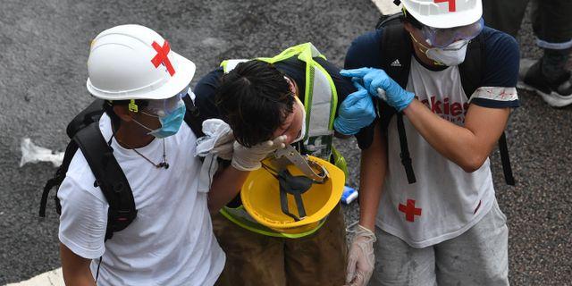 En demonstrant får hjälp efter att ha träffats av tårgas. ANTHONY WALLACE / AFP