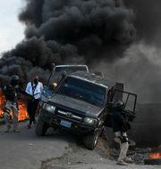 Polisen överger sitt fordon efter att en demonstration till stöd för den mördade presidenten urartat.  Matias Delacroix / TT NYHETSBYRÅN