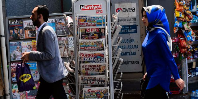 Människor går förbi en tidningskiosk i Istanbul på måndagen.  YASIN AKGUL / AFP