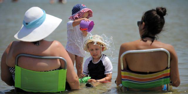 Personer som badar. Stephen B. Morton / TT NYHETSBYRÅN