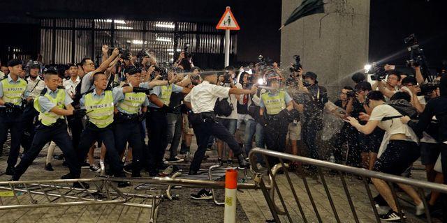 Poliser använder pepparsprej mot demonstranter. Vincent Yu / TT NYHETSBYRÅN/ NTB Scanpix