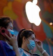Illustrationsbild: Två kvinnor utanför Apples flaggskeppsbutik i Beijing.  Ng Han Guan / TT NYHETSBYRÅN