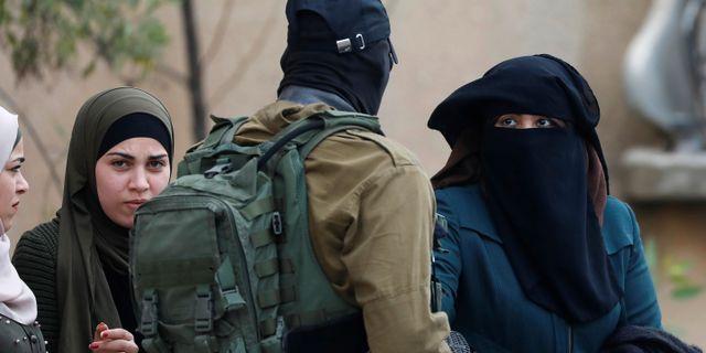 Israelisk soldat stoppar förbipasserande palestinier i jakten på gärningsmannen. MOHAMAD TOROKMAN / TT NYHETSBYRÅN