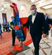 Två män bär en kraschad Superman-docka inför misstroendeomröstningen i det rumänska parlamentet i Bukarest. Andreea Alexandru / TT NYHETSBYRÅN