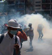 Demonstranter flyr från tårgas under en demonstration TT NYHETSBYRÅN