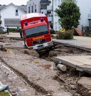En brandbil har fastnat i ett hål i en väg. Philipp von Ditfurth / TT NYHETSBYRÅN