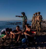 Spansk gränspolis omhändertar migranter på stranden vid exklaven Ceuta. Bernat Armangue / TT NYHETSBYRÅN