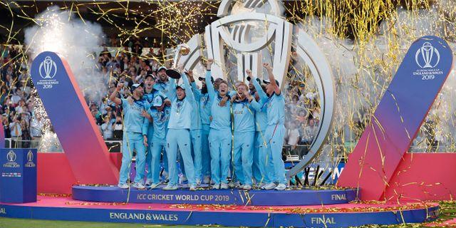 Englands kapten Eoin Morgan lyfter pokalen tillsammans med guldlaget. Matt Dunham / TT NYHETSBYRÅN