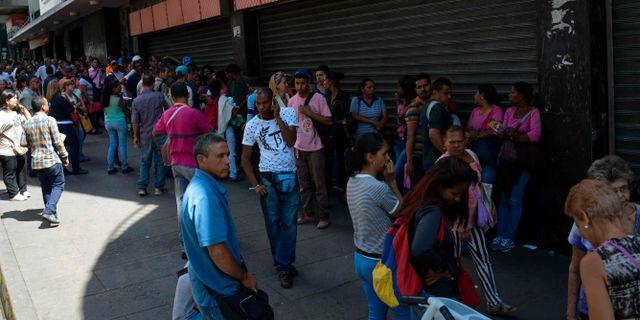 Människor köar för att köpa basvaror i en matbutik i Caracas under krisen. FEDERICO PARRA / AFP