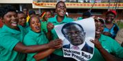 Flera personer håller upp en affisch på Emmerson Mnangagwa. Ben Curtis / TT / NTB Scanpix