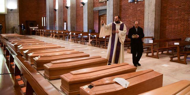 Prästen don Marcello välsignar avlidna i kyrkan San Giuseppe i Seriate. PIERO CRUCIATTI / TT NYHETSBYRÅN