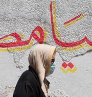 """En kvinna med ansiktsmask framför en vägg där det står """"länge leve Egypten"""". AMR ABDALLAH DALSH / TT NYHETSBYRÅN"""
