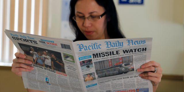En hotellreceptionist i Tamuning i Guam läser om Nordkoreakrisen i tidningen Pacific Daily News.  ERIK DE CASTRO / TT NYHETSBYRÅN